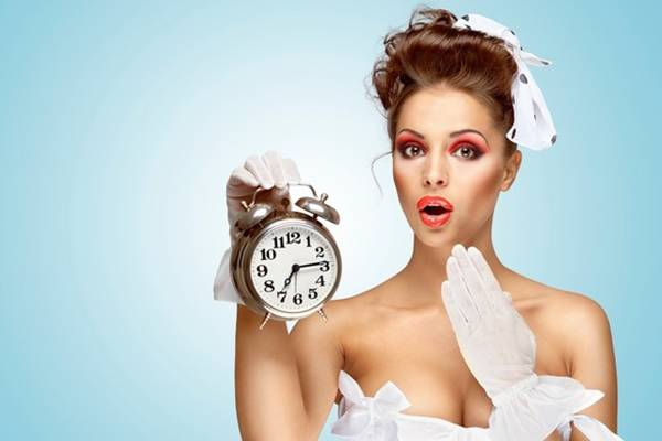 A beautiful vintage girl in a white wedding dress being late in the morning and holding a retro alarm clock in her hand.
