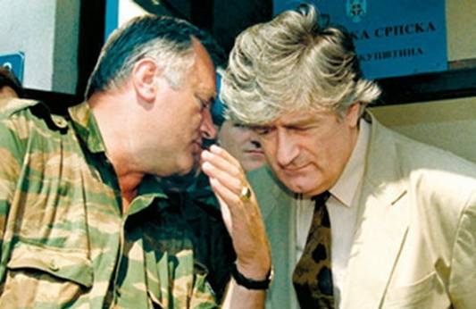 (FILES) Ratko Mladic (L), Bosnian Serb military commander whispers 05 August 1993 in Serb stronghold of Pale, to the ear of Radovan Karadzic, Bosnian Serb warlord and leader of the Serb-run part of Bosnia during the 1992-1995 war. Top Bosnian Serb war crimes fugitive Ratko Mladic was arrested in Belgrade 21 February 2006, more than a decade after he was indicted for ordering the Srebrenica massacre, B92 radio quoted an unofficial source as saying. Mladic was arrested in the Serbian capital before being transferred to the northern Bosnian town of Tuzla, the independent B92 radio station reported, saying the information came from several sources. AFP PHOTO FILES